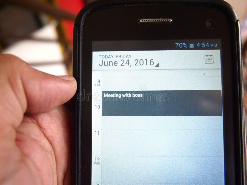 Hand die een smartphone met een kalenderherinnering houden stock foto