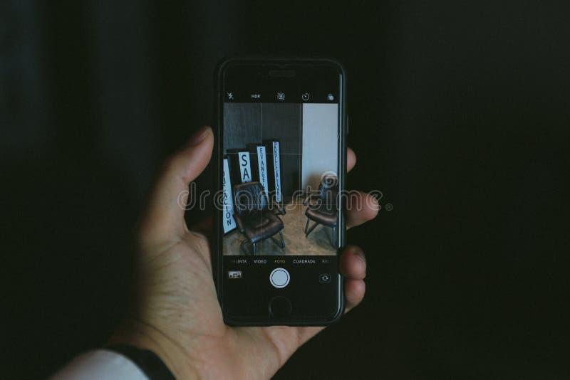 Hand die een smartphone op een camerawijze houden die sommige affiches schieten royalty-vrije stock afbeeldingen