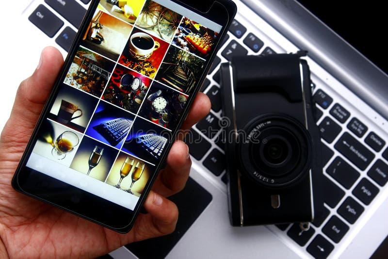 Hand die een smartphone over een digitale mirrorless camera en laptop computer houden royalty-vrije stock foto's