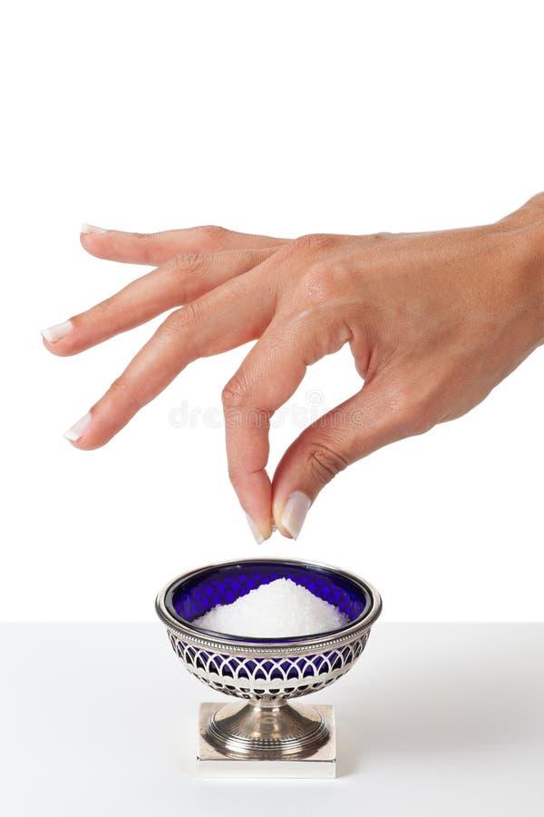 Hand die een snuifje van zout grijpen stock fotografie