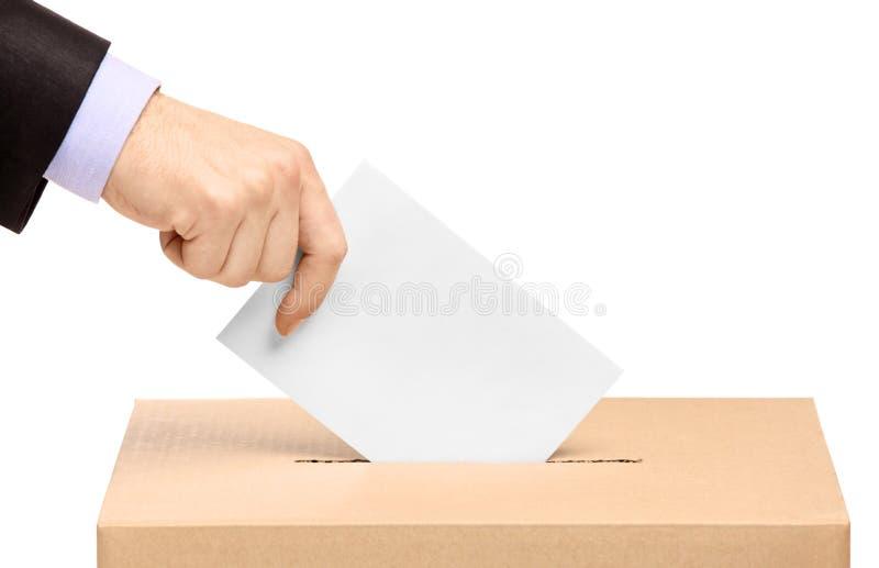 Hand die een stemmingsstemming in een groef van doos zet stock foto