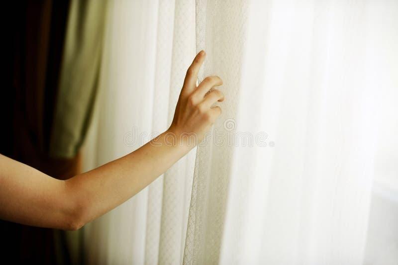 Hand die een venstergordijn trekken stock fotografie