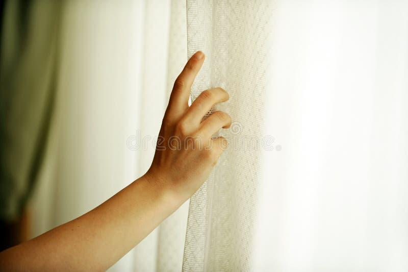 Hand die een venstergordijn trekken stock foto