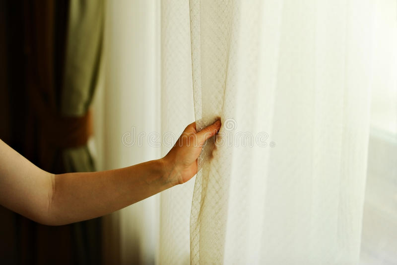 Hand die een venstergordijn trekken royalty-vrije stock foto