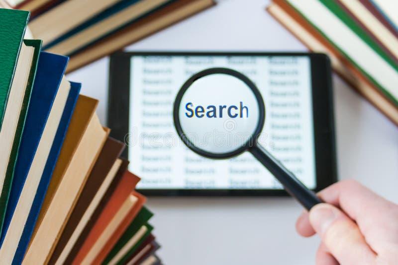 Hand die die een vergrootglas over een tablet houden door boek wordt omringd stock fotografie