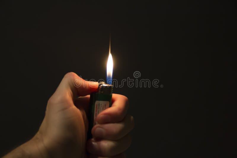 Hand, die ein beleuchtetes Feuerzeug in der Dunkelheit hält stockfotografie