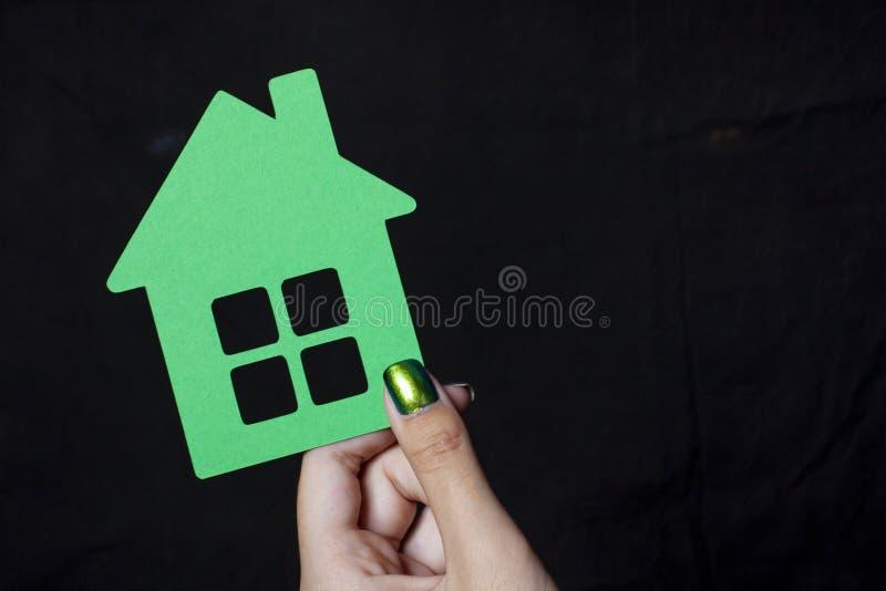 Hand, die ein kleines Grünbuchhaus hält stockbild