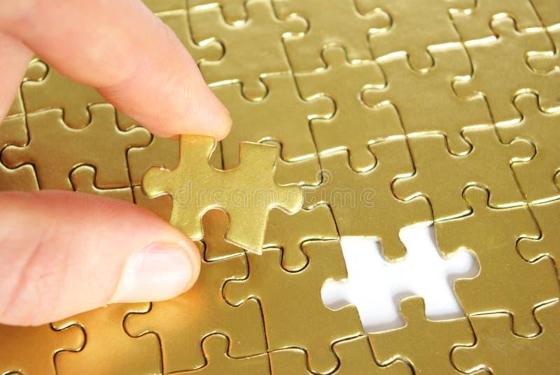 Hand, die ein Puzzlespiel anhält lizenzfreie stockfotos