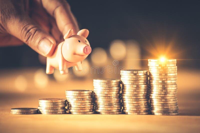 Hand, die ein Sparschwein auf Münzenstapel hält Kreative Ideen für die Rettung des Geldkonzeptes stockfoto