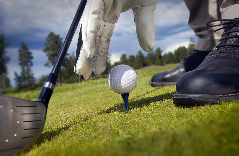Hand, die ein T-Stück mit Golfball setzt lizenzfreie stockbilder