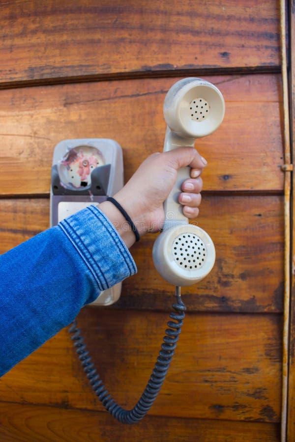 Hand, die ein weißes Weinlesetelefon hält stockbild