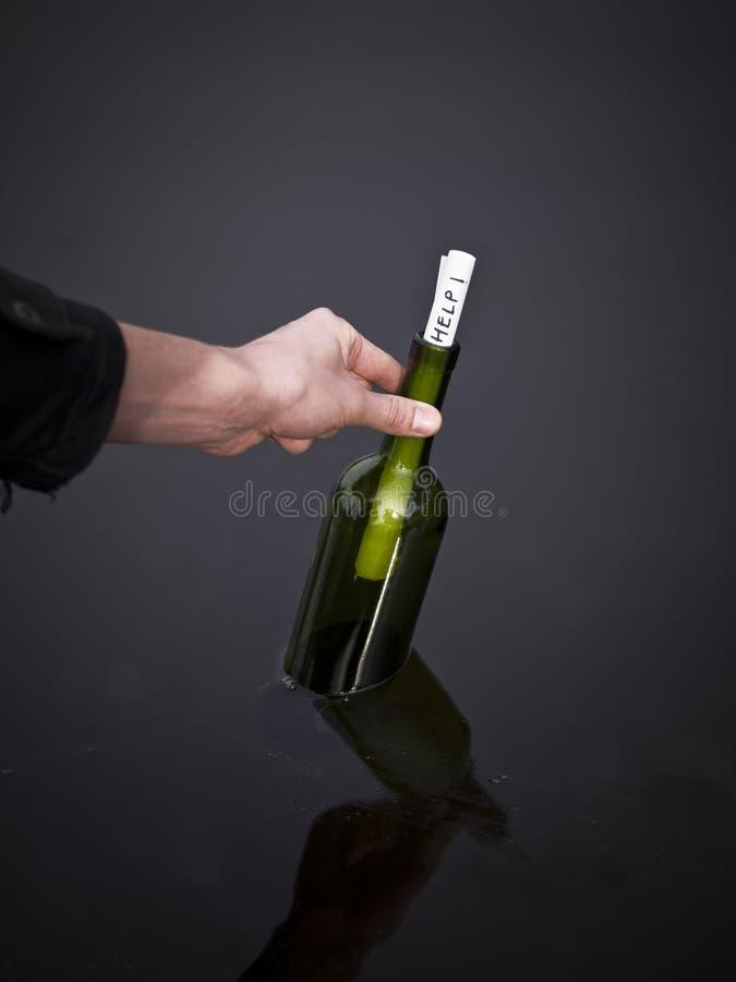 Hand, die eine Flasche aufhebt lizenzfreie stockfotografie