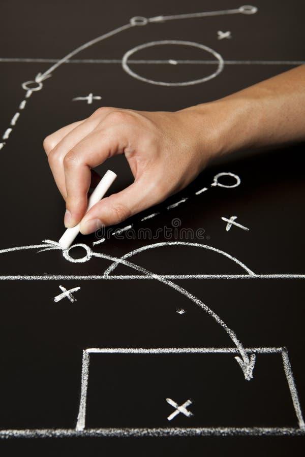 Hand, die eine Fußballspielstrategie zeichnet