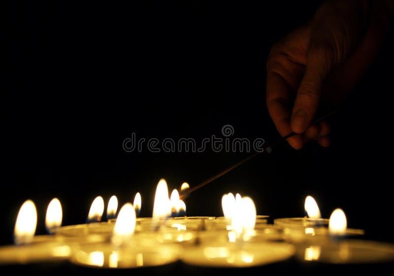 Hand, die eine Kerze beleuchtet stockfotografie