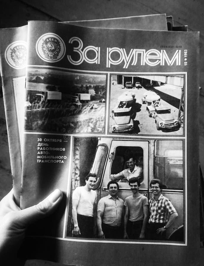 Hand, die eine russische Zeitschrift hinter dem Rad h?lt lizenzfreie abbildung