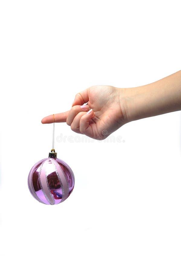 Hand, die eine Weihnachtsverzierung anhält lizenzfreies stockbild