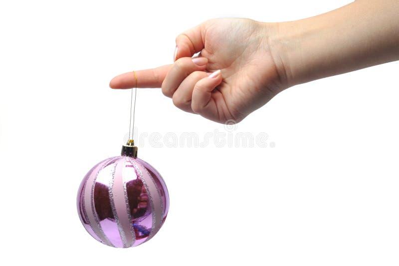 Hand, die eine Weihnachtsverzierung anhält stockbild