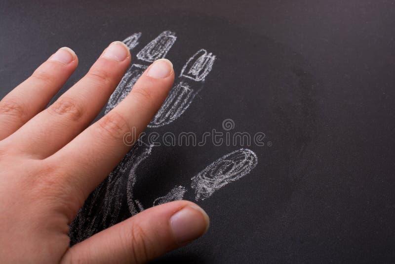 Hand, die einem handprint gezeichnet durch Kreide auf Tafel ähnelt stockfotos