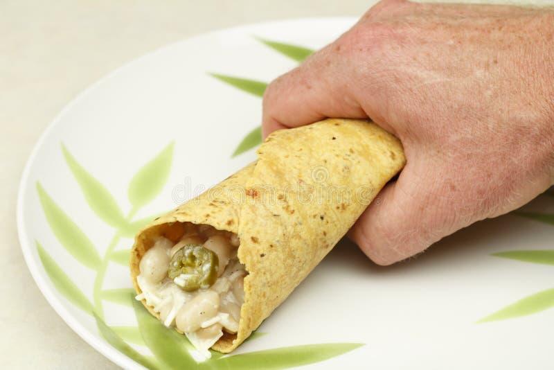 Hand, die einen Burrito anhält stockfoto