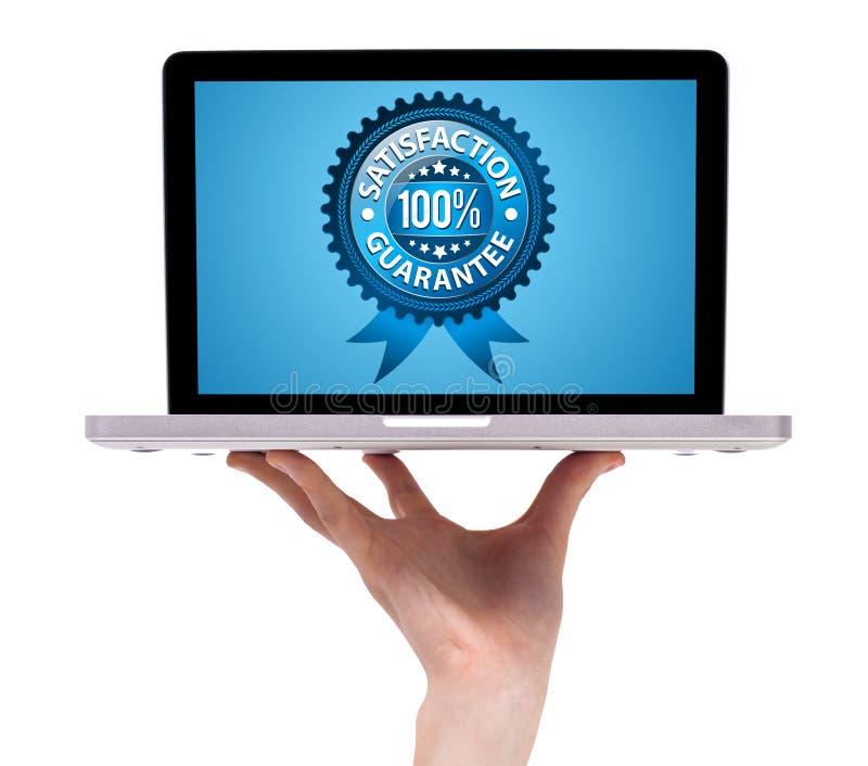 Hand, die einen Laptop mit Zufriedenheits-Garantie anhält stockfotografie