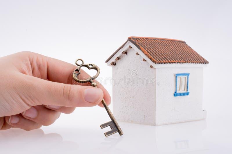 Hand, die einen Schlüssel nahe einem Haus hält stockbild