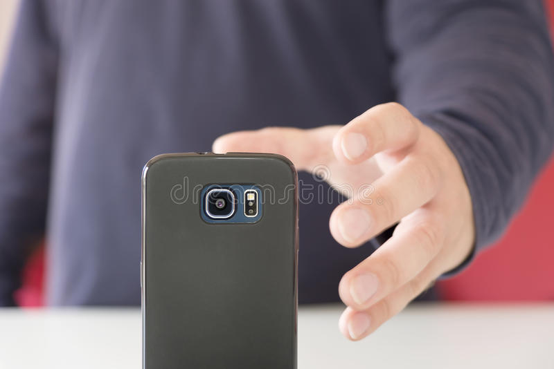 Hand, die einen Smartphone greift stockfotos