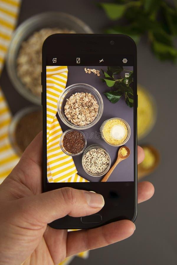 Hand, die einen Smartphone macht ein Bild von den verschiedenen ungekochten Getreide hält Verschiedene Arten von Grützen in den S stockfoto