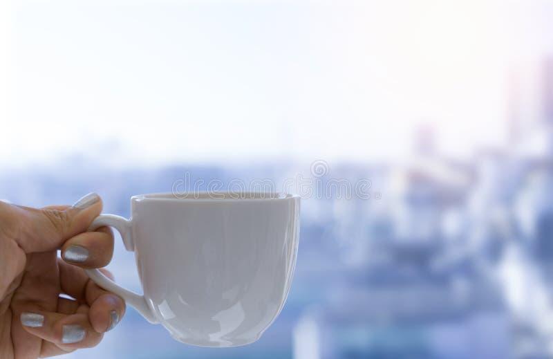 Hand, die einen Tasse Kaffee auf Stadthintergrund hält stockbilder
