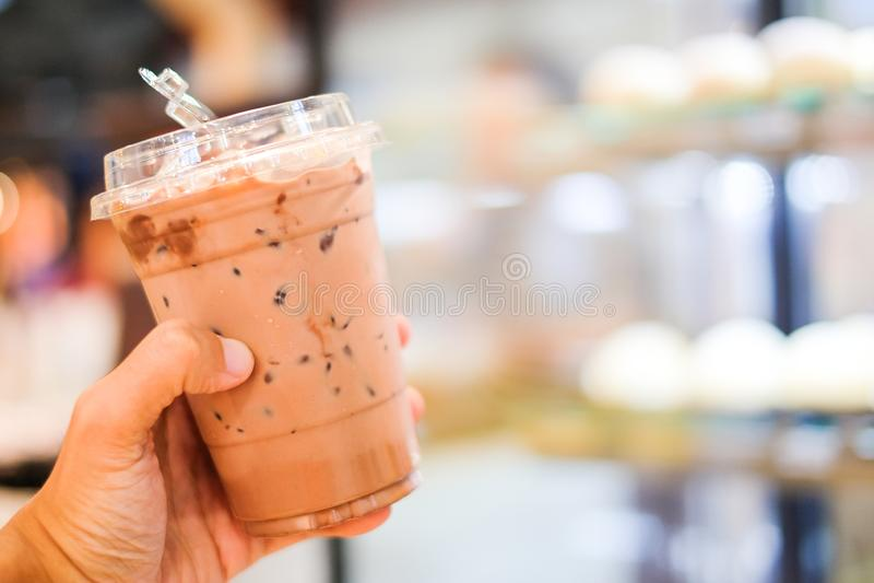 Hand, die Eiskakao oder Kaffee Latteespresso oder -cappuccino hält lizenzfreie stockfotografie