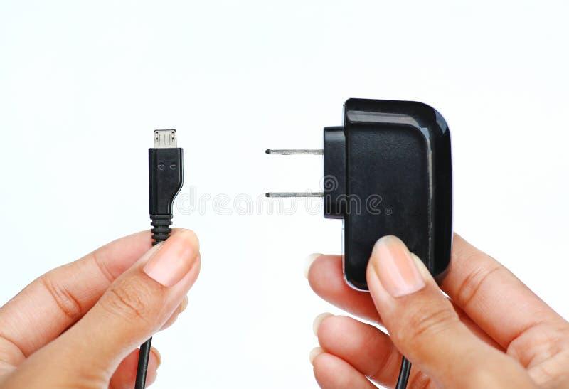 Hand die Elektrische stop en micro- usb kabel op witte achtergrond houden royalty-vrije stock foto