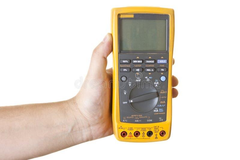 Hand die elektronische multimeter houdt stock afbeelding