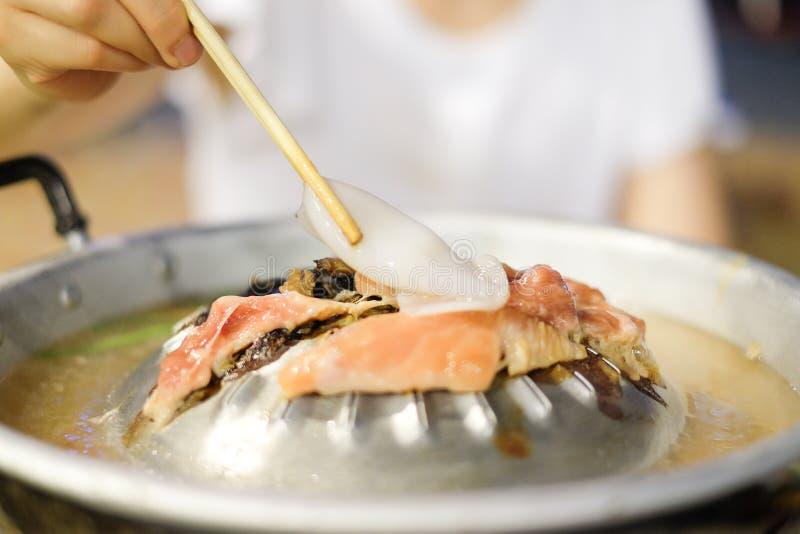 Hand, die Essstäbchen mit Kalmar für gegrillt hält lizenzfreie stockfotografie