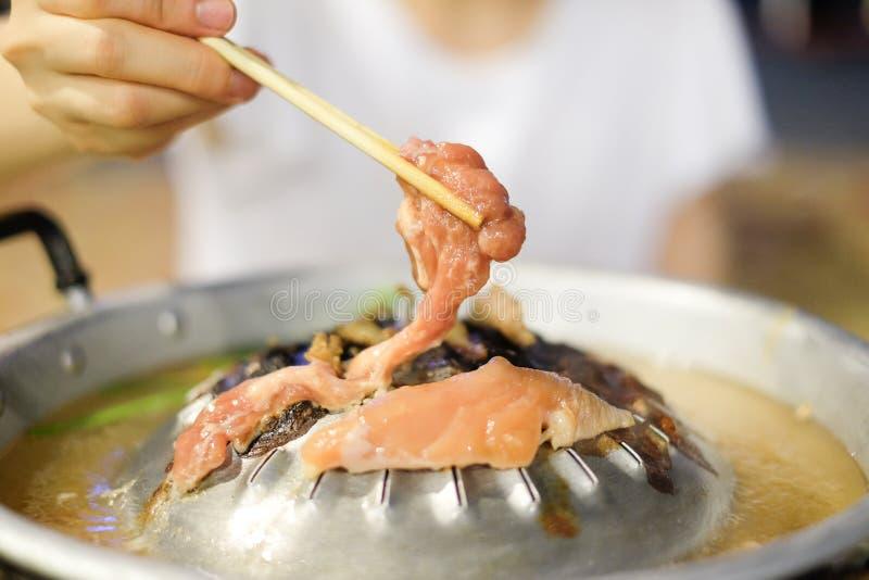 Hand, die Essstäbchen mit Schweinefleisch hält stockfoto