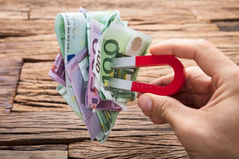 Hand die Euro Papernotes met Magneet op Houten Lijst trekken stock foto