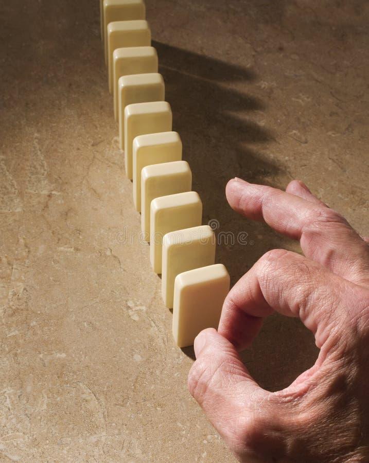 Hand die in evenwicht om wordt gehouden om domino's neer te halen stock afbeeldingen