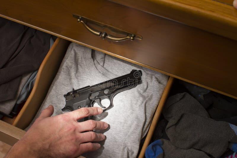 Hand, die für Pistole erreicht lizenzfreie stockbilder