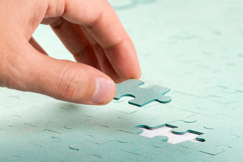 Hand, die fehlendes Stück des Puzzlen einsteckt lizenzfreie stockfotos
