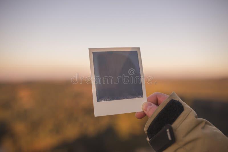 Hand, die frische sofortige Fotografie, aus Fokusbergen im Hintergrund heraus hält lizenzfreie stockfotos