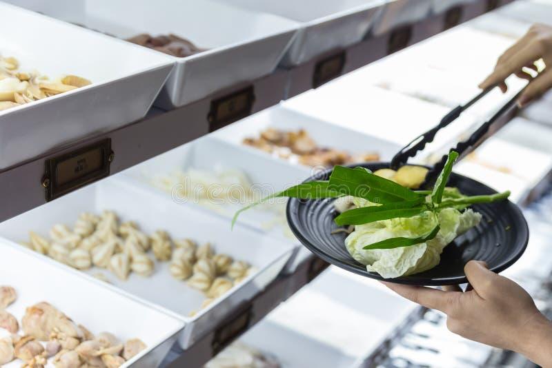 Hand, die Frischgemüse im Schwarzblech von der Nahrungsmittellinie für sukiyaki Buffet im Kühlschrank ausgewählt und geklemmt wor lizenzfreies stockbild