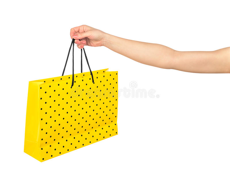 Hand, die gelbe Geschenktasche hält stockfoto