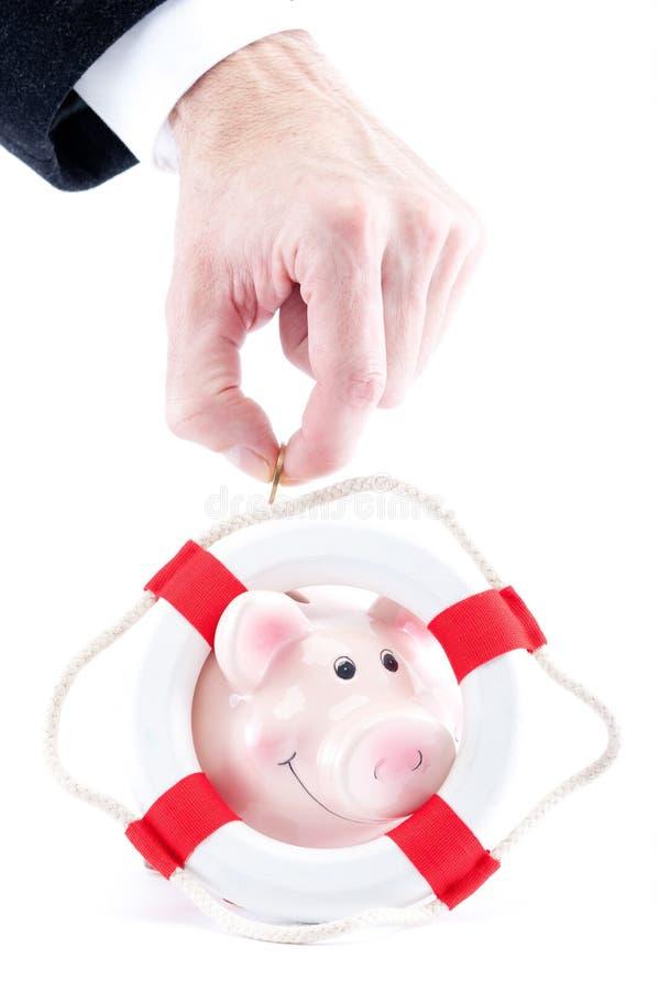 Hand, die Geld auf eine Piggyquerneigung steckt stockbilder