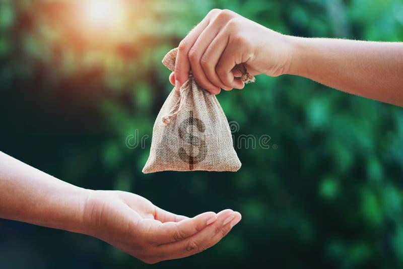 hand die geldzak geven aan een andere mensen op groene achtergrond met zonsopgang royalty-vrije stock afbeeldingen