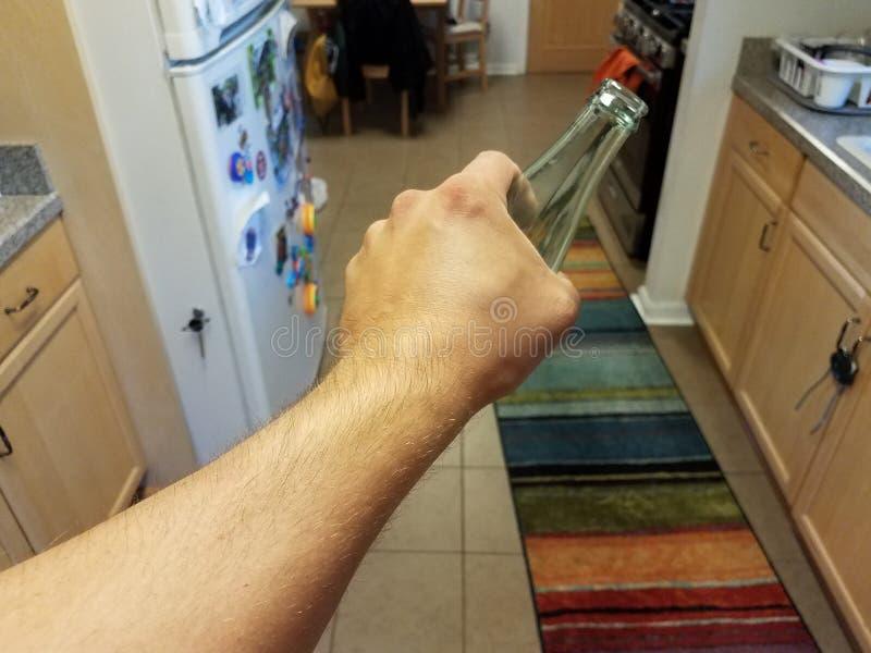 Hand, die Glasgetränkeflasche in der Küche hält stockfotografie