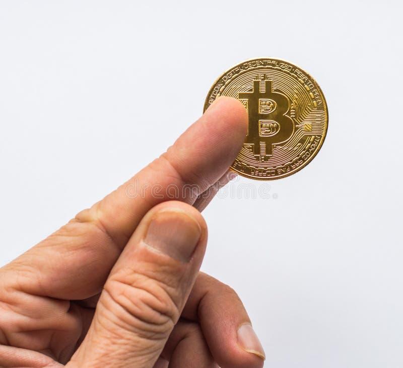 Hand, die goldenes virtuelles Geld Bitcoin hält stockfotos