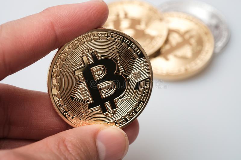 Hand die gouden bitcoincryptocurrency op witte achtergrond houden stock afbeelding