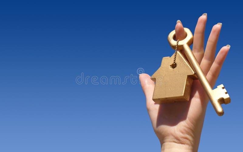 Hand die gouden sleutel houdt stock afbeeldingen