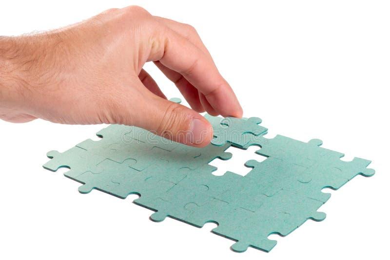 Hand, die grünes Puzzlen einsteckt lizenzfreie stockfotografie