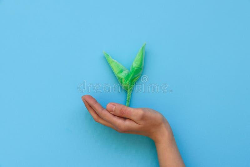 Hand die groene die spruit houden van plastic beschikbare pakketten op blauwe achtergrond wordt gemaakt Sparen de creatieve werel royalty-vrije stock foto's