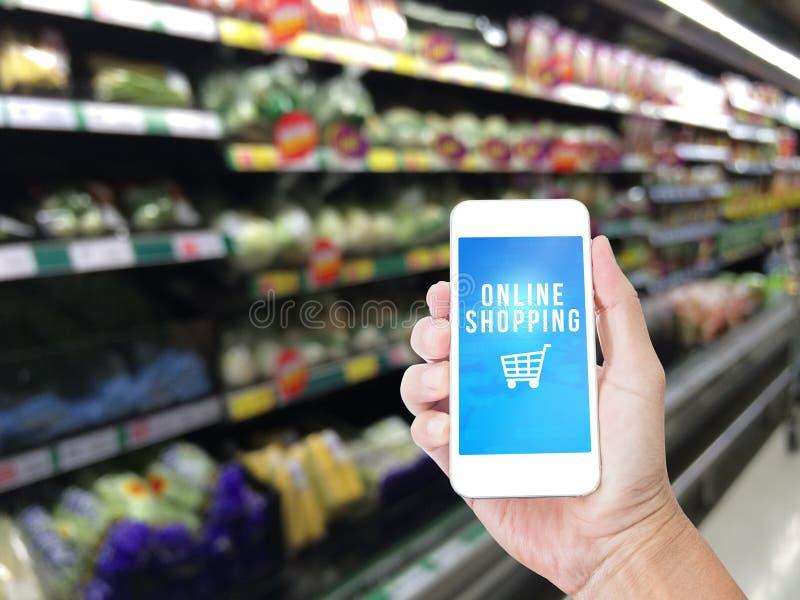 Hand, die Handy mit on-line-Einkaufswort hält stockfoto
