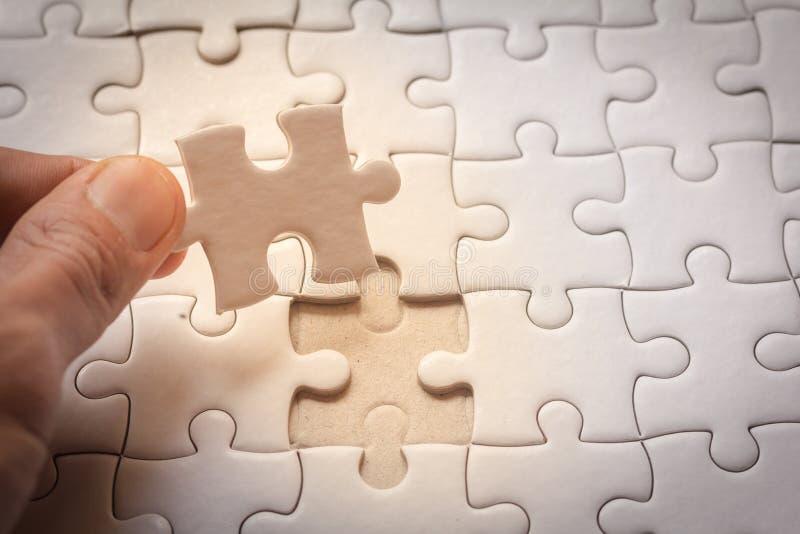 Hand die het laatste puzzelstuk plaatsen, stock afbeelding